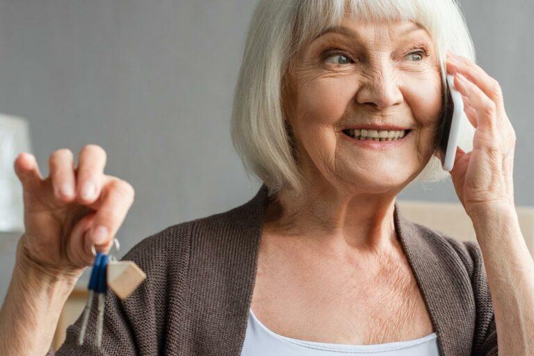 The Philomena | Senior woman speaking on smartphone and holding keys