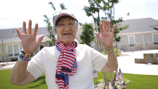 The Philomena   Senior wearing a red, white, and blue scarf and hat while smiling